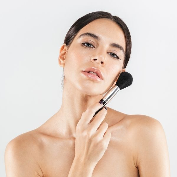 девушка с кистью для макияжа у лица