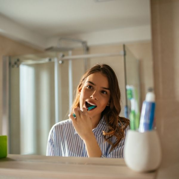 девушка чистит зубы перед зеркалом