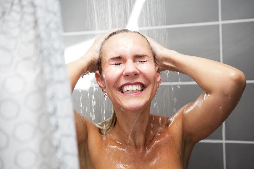 улыбающаяся женщина принимает душ