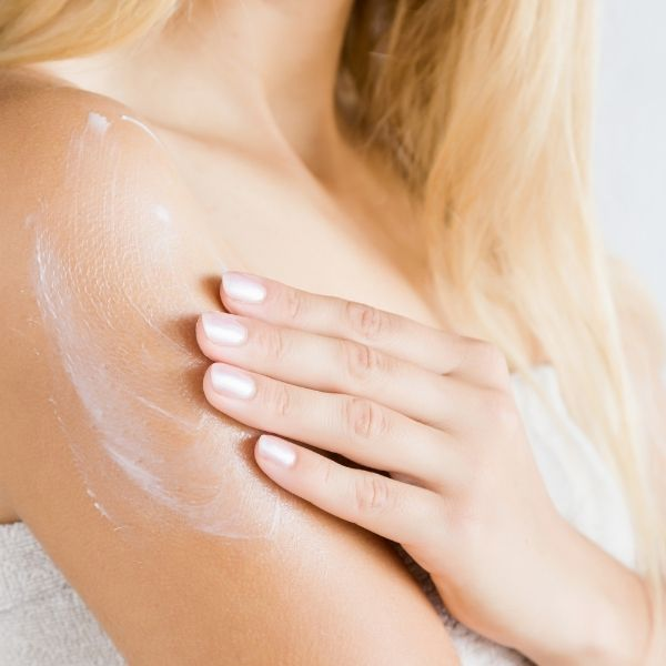 woman is applying cream
