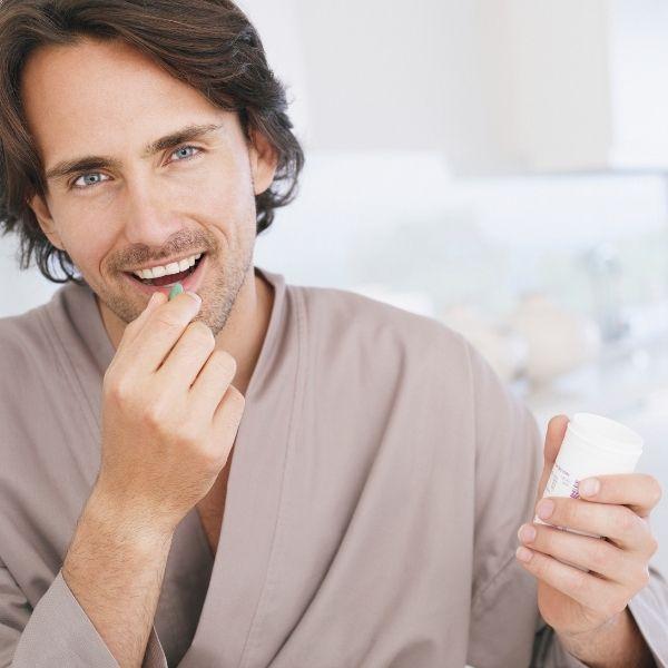 мужчина ест таблетку