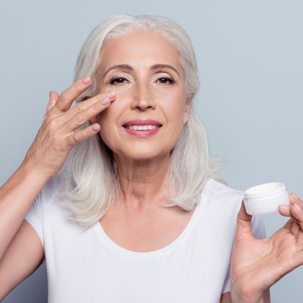 женщина в возрасте наносит крем под глаза