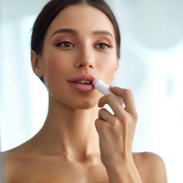 woman is applying lip balm