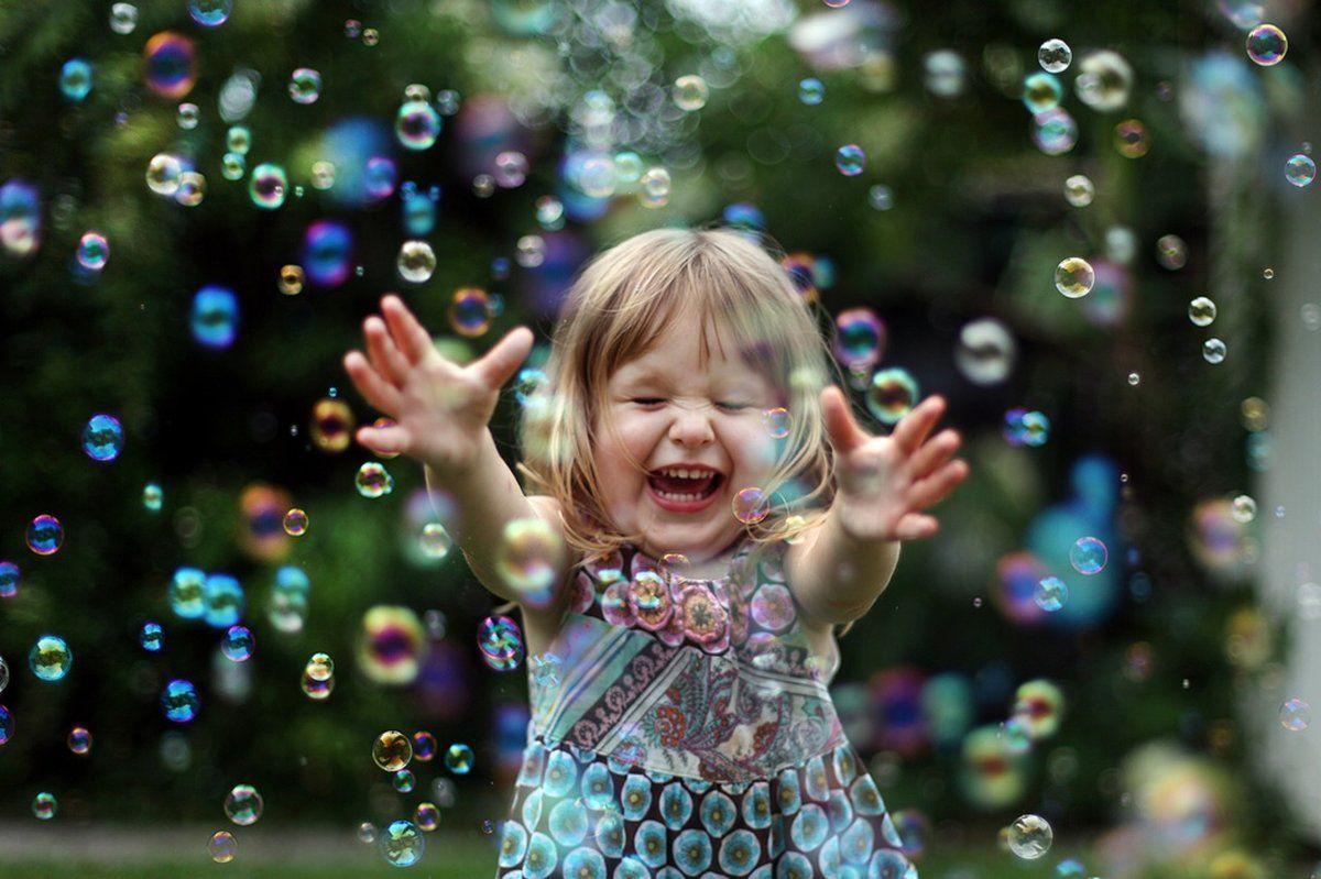девочка радуется мыльным пузырям