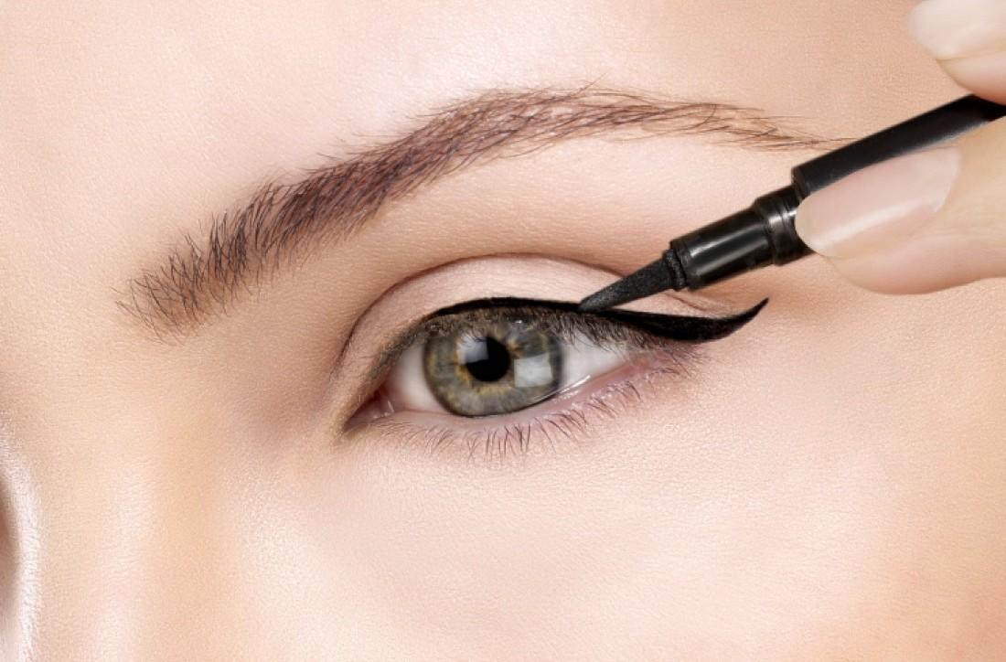 woman is using eyeliner